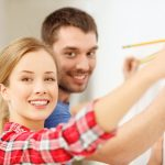 26694838 – repair, building and home concept – smiling couple measuring wall